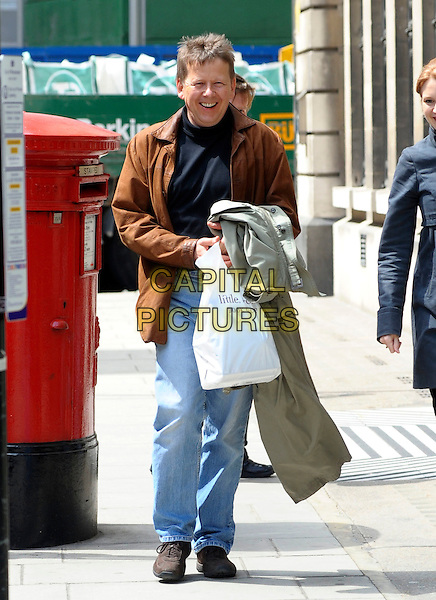 BILL TURNBULL.Arriving at the BBC, London, England..May 14th, 2010.full length jeans denim black top brown leather plastic bag jacket .CAP/DYL.©Dylan/Capital Pictures.