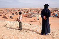 "A couple observe ""February 27"" wilaya on December 12, 2003, in the Saharawi refugee camps. Saharawi people have been living at the refugee camps of the Algerian desert named Hamada, or desert of the deserts, for more than 30 years now. Saharawi people have suffered the consecuences of European colonialism and the war against occupation by Moroccan forces. Polisario and Moroccan Army are in conflict since 1975 when Hassan II, Moroccan King in 1975, sent more than 250.000 civilians and soldiers to colonize the Western Sahara when Spain left the country. Since 1991 they are in a peace process without any outcome so far. (Ander Gillenea / Bostok Photo)"