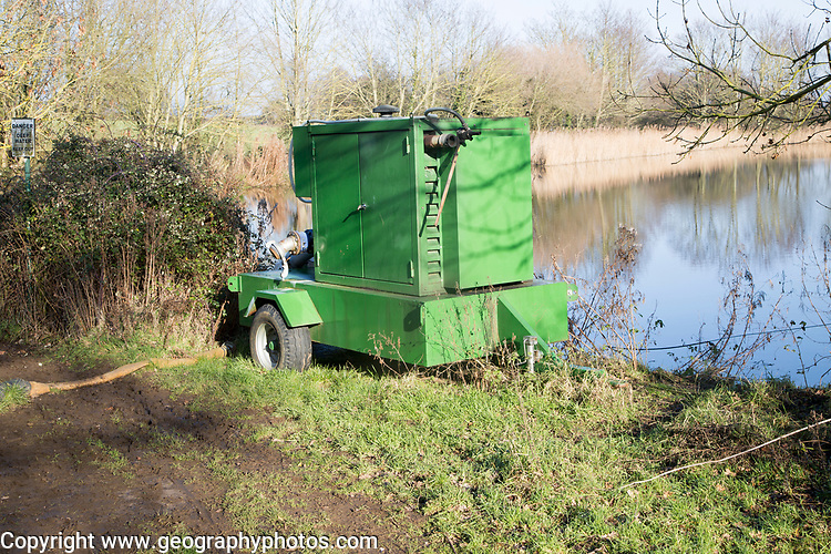 Irrigation water pump machine by lake pond pool, Waldringfield, Suffolk, England, UK