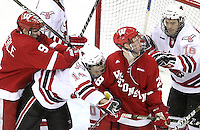 Wisconsin's Mark Zengerle sends UNO's Joey Martin into teammate Jordy Murray during the second period. Zengerle was whistled for roughing on the play. At right is UNO's Johnnie Searfoss. No. 16 UNO beat No. 7 Wisconsin 4-3 Saturday night at Qwest Center Omaha. (Photo by Michelle Bishop)