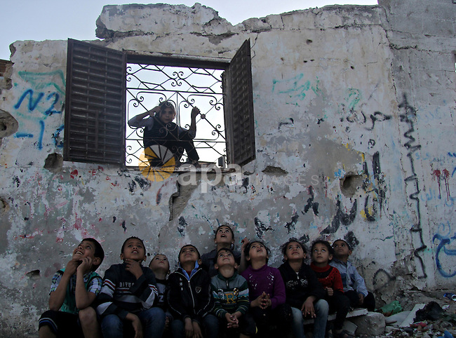 Palestinian children play around their houses which destroyed during the 50-day war between Israel and Hamas militants in the summer of 2014, in the Gaza Strip town of Beit Hanun on April 25, 2015. Photo by Nidal Alwaheidi