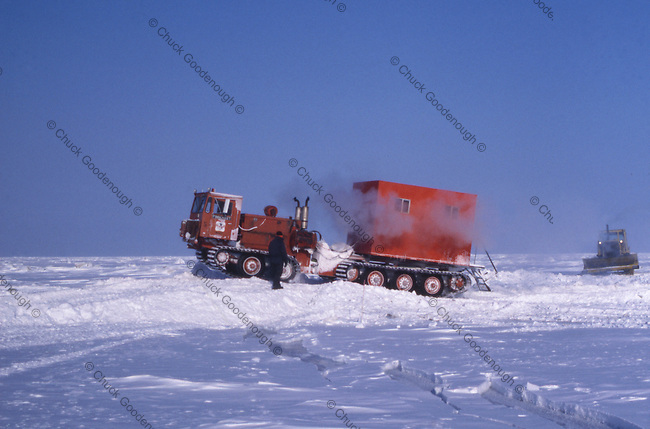 After building a snow bridge to disperse weight, housing and equipment trailers are towed safely over a crack in the sea ice. Geophysical crews work during the arctic winter when they can travel out onto the ice of the Beafort Sea, north of the coast of Alaska. Photo taken around 1980 of a geophycical recording vehicle on snow tracks.