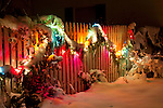 A snow covered, lighted garland decorates a fence at night, Coeur d'Alene, Idaho.
