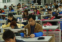 "Workers at General Union Stationary & Gift Co. Ltd, make ""cool Dog"" bags at a Taiwanese-owned factory on the outskirts of Fuzhou City, China..02-MAR-04"