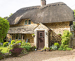 Historic thatched cottage in garden at village of Sandy Lane, Wiltshire, England, UK