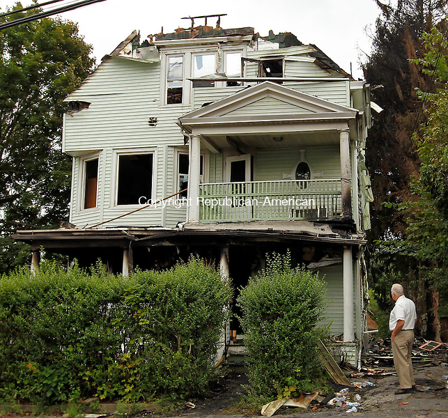 Waterbury, CT- 15, August 2010-081510CM10  A man stands outside a 3 apartment house on Hill Street in Waterbury that was destroyed by a fire late Saturday night.  A family of three was displaced and was seeking aid from the Red Cross.  The fire remains under investigation.  Christopher Massa Republican-American