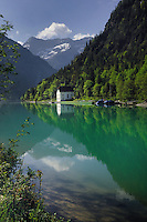 Cottage, marina, trees and reflections in Lake Plansee near Reutte, Austrian Alps. Austria.