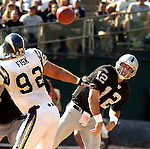 Oakland Raiders quarterback Rich Gannon (12) passes past San Diego Chargers defensive tackle Jason Fisk (92) on Sunday, September 28, 2003, in Oakland, California. The Raiders defeated the Chargers 34-31 in overtime.
