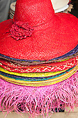 Quatre Bornes, Mauritius. Red straw hat and others for sale at the market.