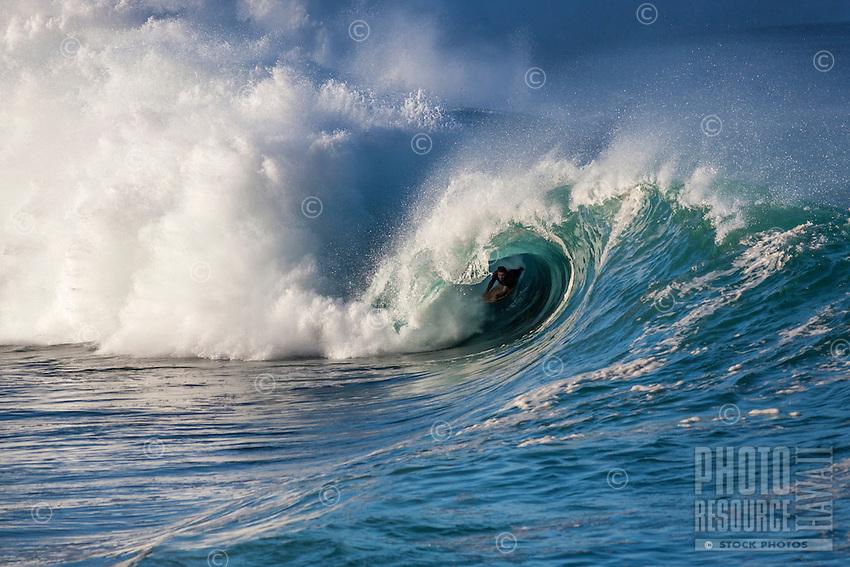 A bodyboarder rides a big hollow wave at Waimea Shorebreak, North Shore, O'ahu