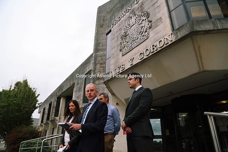 Pictured: DCI Rob Conick of South Wales Police (2nd L)with  DC Sue Davies (L) and other colleagues, reads a statement on the steps of Swansea Crown Court.<br />