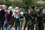 """Palestinian women shout slogans against Israeli troops outside Ofer military prison near the West Bank city of Ramallah on May 1, 2012 during a demonstration in support for prisoners held in Israeli jails. Clashes erupted between stone-throwing youths and the Israeli army, who fired tear gas, rubber bullets and a foul-smelling liquid known as """"skunk"""" to break up the demonstration. Photo by Issam Rimawi"""