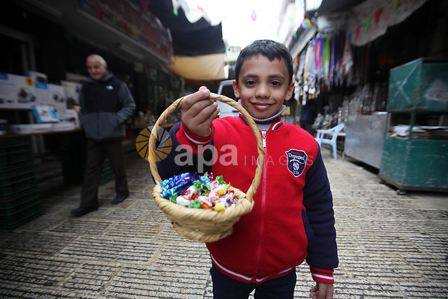 "A Palestinian boy distributes a candy during a ritual ceremony to commemorate the birth of the Prophet Mohammed, known in Arabic as ""al-Mawlid al-Nabawi"", in the West Bank city of Nablus on December 11, 2016. Photo by Nedal Eshtayah"