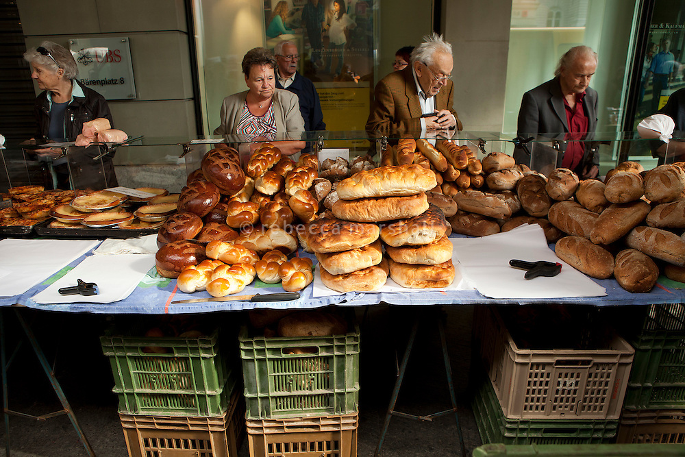 Customers buy loaves of bread at a bakery stall, Schauplatzgasse, Bern, Switzerland, 27 August 2011. Zopf, bread loaves second from left, are a traditional regional bread eaten on Sunday mornings.