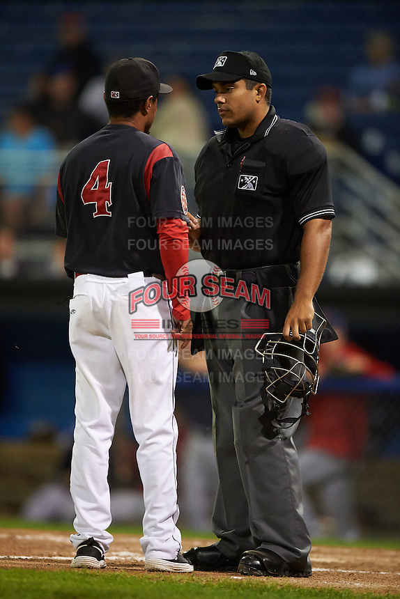 Umpire Jose Matamoros listens to manager Angel Espada (4) during a game between the State College Spikes and Batavia Muckdogs August 23, 2015 at Dwyer Stadium in Batavia, New York.  State College defeated Batavia 5-3.  (Mike Janes/Four Seam Images)