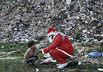 A picture taken on December 27, 2018 shows a Palestinian man Mohammed Abu Hajar, 28, dressed as Santa Claus gives a gift for a child at Nahr al-Bared refugee camp in Khan Younis in the southern Gaza Strip. Photo by Sanad Latifa
