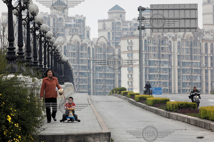 A woman walks with her young son, who rides on child's toy. Behind them is a new housing development.