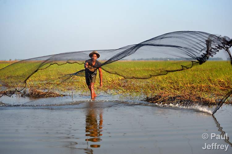 Mao Soeung throws a fishing net in the village of Chek Angkor in northern Cambodia.