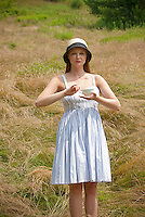 Young woman standing in field holding tea cup