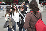 Spanish teenagers pose for photos of their group in Trafalgar Square, London, England.