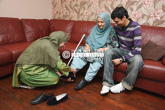 South Asian woman helping her mother put on her shoes.