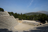 EPIDAURUS, GREECE - APRIL 15 : A view from above of the Theatre, on April 15, 2007 in Epidaurus, Greece. The Theatre, designed by Polykleitos the Younger, was built in the late 4th century BC and extended in the Hellenistic period. It was rediscovered in 1881 and significantly restored in the 1950s.  It has the three main features of a Greek theatre: the orchestra, a sunken round stage; the skene, a raised rectangular stage; and the cavea, a raked semi-circular auditorium with radiating diazomas. To the right is the entrance to one of the two paradoi, or corridors, which gave the actors access to the stage. The theatre is renowned for its accoustics thanks to the symmetry of the cavea, and for its beautiful mountain view, seen here in the morning light. (Photo by Manuel Cohen)