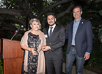 Christopher Silva and Lupe Silva accept the posthumous award for Service to the College on behalf of Jose Silva '84 at the 2019 Alumni Seal Awards at Collins House on Friday, June 21, 2019 during Alumni Reunion Weekend. Brad Fauvre '87, Trustee and president of the Occidental College Alumni Association's Board of Governors stands beside them.<br />