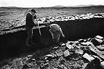 Two men cutting peat on a stretch of land at Loch Portan on the island of North Uist in the Outer Hebrides, Scotland. Peat cutting was a traditional method of gathering fuel for the winter in the sparsely-populated areas on Scotland's west coast and islands. The peat was dried and used in fires and ovens.