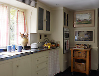 In the kitchen simple cream-painted wooden cupboards are offset with fresh red-and-white checked curtains