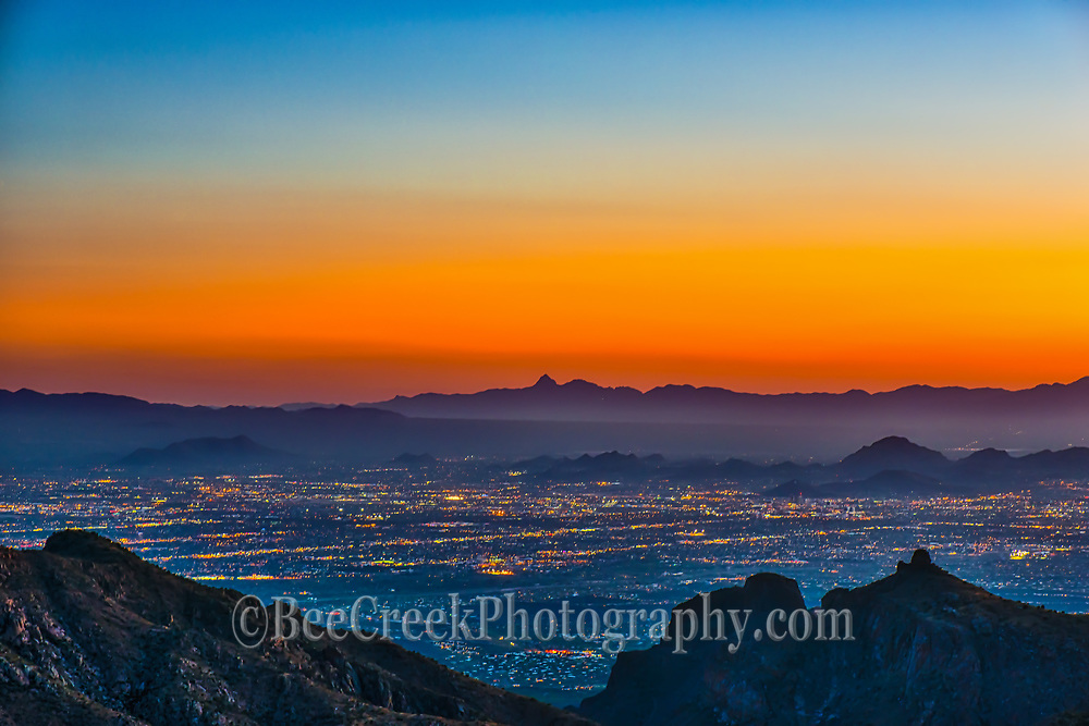 Colorful Sunset over Tucson taken from the Santa Catalinas mountains.  You can see the city light below as they begin to light up at dusk.  I love the desert landscape it so pretty especially with this orange glow over the mountains in the distance. This area is part of the desert Southwest  and if you mean dry it is that, but not empty there are plenty of cacti plants to keep you on the straight and narrow path.
