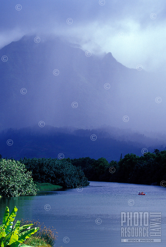 Couple paddling kayak on the Hanalei River with ran shrouded Mount Waialeale in background, Kauai, Hawaii
