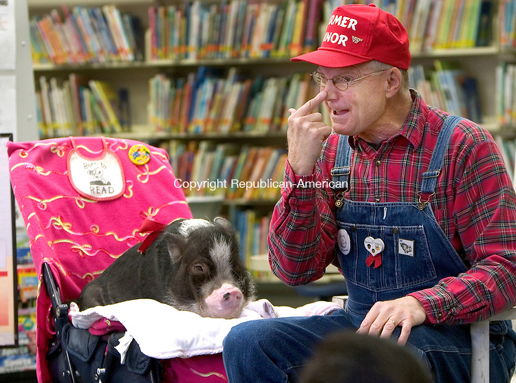 WOLCOTT, CT. 09 February 2010-020910SV04--Farmer Paul Minor of Bristol talks about Daisy&rsquo;s snout during a library program called &ldquo;Pig Out On Reading&rdquo; at the library in Wolcott Tuesday. Farmer Minor&rsquo;s pig Daisy sits in a carriage, at left.<br /> Steven Valenti Republican-American