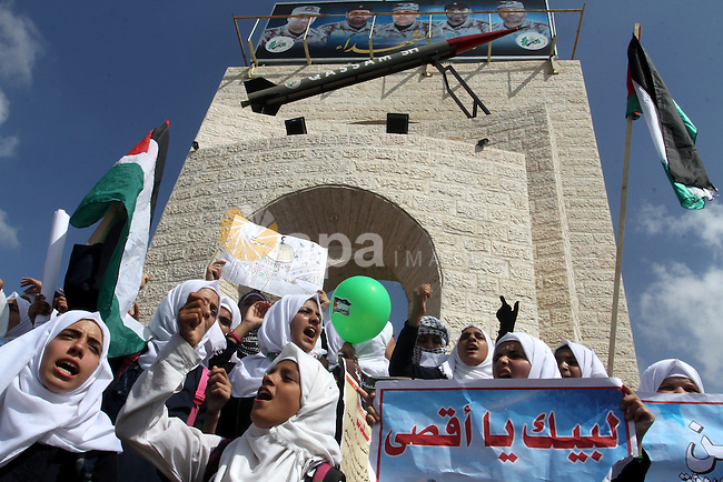 Palestinian schoolgirls shout slogans in front of a mock Qassam rocket during an anti-Israel protest in the southern Gaza Strip town of Rafah on October 14, 2015. Amid violent protests and a wave of stabbings spreading fear in Israel and warnings that a full-scale uprising could erupt, a new generation of Palestinians has been leading the unrest. Photo by Abed Rahim Khatib