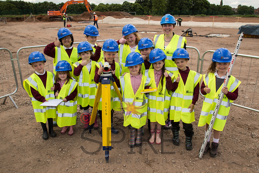 Children from Abbey Primary School don hard hads and Hi-viz to survey the site of their new £4 Million School bing built by Nottingham-based Kier Construction. Pictured with the children is School Head Kim Wakefield