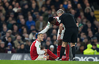 Danny Welbeck of Arsenal and Referee Martin Atkinson check on injured Jack Wilshere of Arsenal during the Carabao Cup semi final 1st leg match between Chelsea and Arsenal at Stamford Bridge, London, England on 10 January 2018. Photo by Andy Rowland.