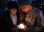Melanie Zavala, 14, lights a candle for Jorge Cerda, 13, at a candlelight vigil at Sparks Middle School in Sparks, Nev., on Wednesday, Oct. 23, 2013. Hundreds of students and community members attended the vigil in honor of slain teacher Michael Landsberry and two 12-year-old students who were injured after a fellow student open fire at the school on Monday, before turning the gun on himself. (AP Photo/Cathleen Allison)