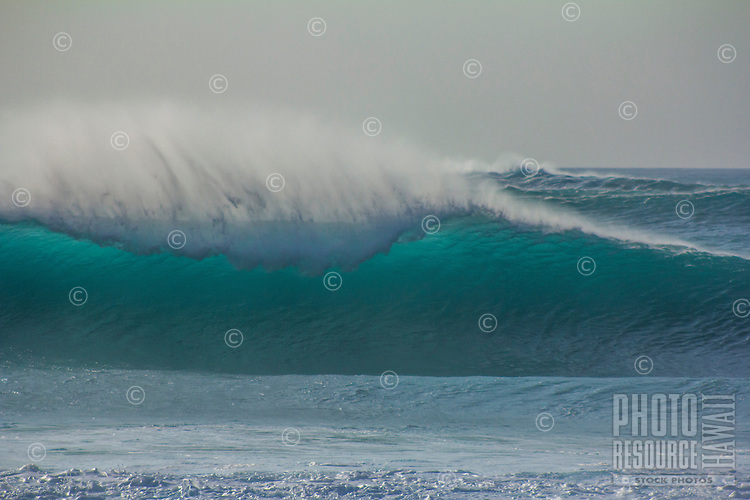 A large wave lights up from the afternoon sun and is blown by strong offshore winds at Pipeline on the North Shore of O'ahu.