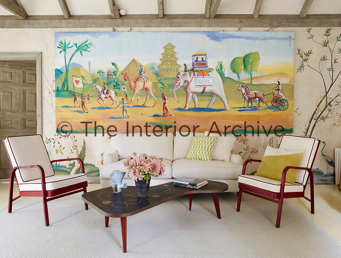 Two retro armchairs and a deep sofa are arranged around a 1950s Berthold Müller cocktail table. The exposed beamed ceiling and wallpaper, a faded botanical print, which has been bleached by years of bright sun, give the room a rustic feel.