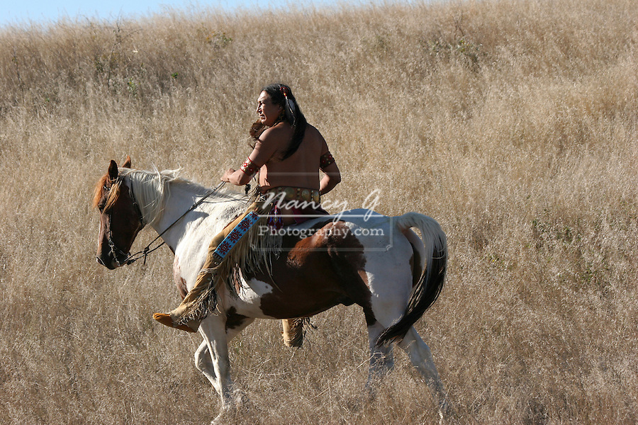 A Native American Indian riding horseback scouting for ememies through the prairie of South Dakota