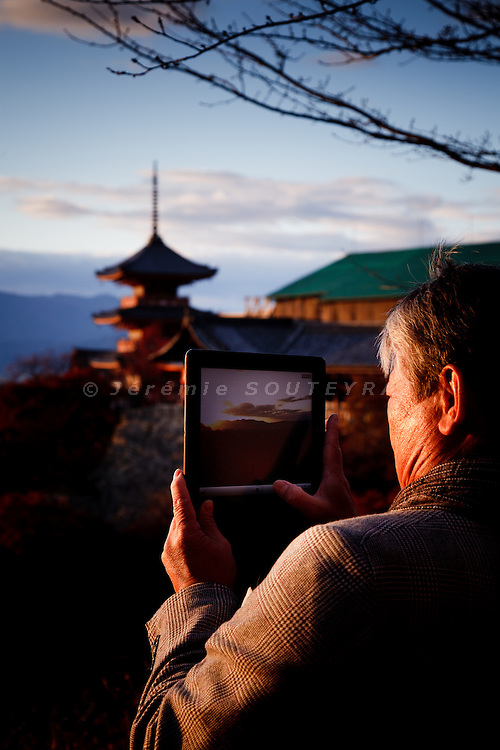 Kyoto, November 24 2011 - At Kiyomizu-dera in Kyoto. A Japanese man taking pictures with his ipad.