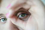 Close-up of a woman looking through her fingers