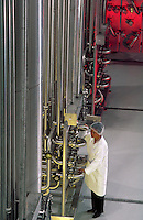 A technician examines equipment at a water bottling plant.