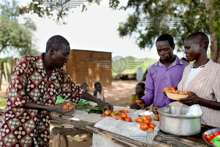 A man buying tomatoes at the small village market at Ifoho Boma. The market is the only source of income for some families in the community, and the paucity of goods on sale underscores both the lack of produce available, and the weak purchasing power of village residents.