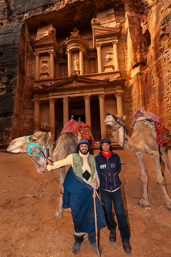 Bedouin men with their camels, with the Treasury monument behind, Petra, Jordan.