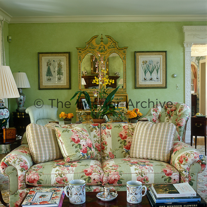 In the drawing room fresh green walls are the perfect backdrop for pretty yellow-painted antique writing desk and a comfortable sofa covered in a traditional chintz of sprawling pink cabbage roses