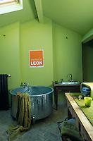 An unuusual round zinc bathtub stands in this bright green bathroom