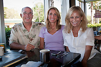"""Dave Ettinger, CEO/Publisher, Nita Ettinger, Operations/Associate Editor and Debi Pittman Wilkey discuss """"Top Ten"""" photo details for the Summer/Fall issues of 'Must Do' travel magazines at Word of Mouth cafe in Sarasota, Florida, USA, May 13, 2010. 'MustDo' travel magazines are published by Siesta Publications/Gannett Magazine Group and distributed throughout the southern Florida area."""