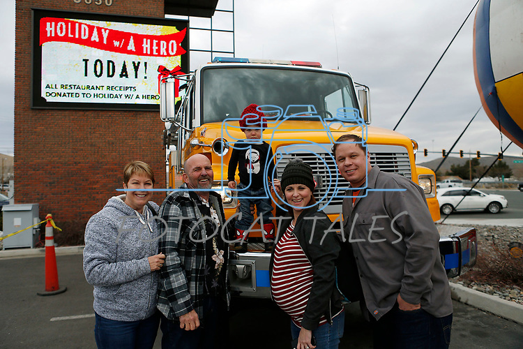 The Shirk and Jacks family takes photos on the fire truck as first responders from around the area wait on diners at Bodines as part of the Feast with a Hero fundraiser in Carson City, Nev., on Saturday, Dec. 15, 2018. <br /> Photo by Cathleen Allison/Nevada Momentum