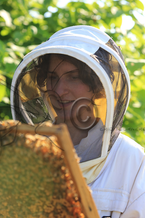 Stephanie Rack, 28 years old, Thônes in Haute-Savoie, posing in the apiary. Great regularity is demanded in managing the production of royal jelly. It's a much less physical job than the production of honey and I can live my life as a young woman in my spare time. I have two productions in the week. A 6-day week. ///Stéphanie Rack, 28 ans, Thônes en Haute-Savoie. Pose au rucher. La production de gelée royale demande une très grande régularité dans la gestion de la production. C'est un métier moins physique que la production de miel et je peux vivre ma vie de jeune femme avec du temps libre. J'ai deux production dans le semaine. Une semaine de 6 jours.