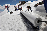 "Rolls of fleece are unwrapped at Brunnenkogel Ferner (Austrian word for glacier).  They are working to keep it from melting.  Workers uncovered rolls of the material and attached it to the top of the part of the glacier.  Covered ice melts slower. <br /> The ski area at 3,400 meters is covered to help save the ski industry since the glacier is retreating.  The cost of materials is one Euro per square meter.<br /> <br /> The Alpine glaciers -- in Austria, Switzerland, France and Italy -- are losing one percent of their mass every year and, even supposing no acceleration in that rate, will have all but disappeared by the end of the century. More hot, dry summers like that of 2003 in Europe, when the loss speeded to five percent, could cut the life expectancy to no more than 50 years, according to Wilfried Haeberli of the University of Zurich...""We estimate that by the end of the 21st century, with a medium-type climate scenario, about five percent of what existed in the 1970s will have survived, he added."